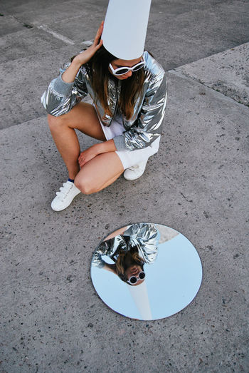 High Angle View Women Lifestyles Outdoors Young Adult Young Women Mirror Reflection Girl Girls Weird Round Shape Round Real People Leisure Activity Sitting Looking Glasses Sunglasses Concrete Weirdo Strange Surreal