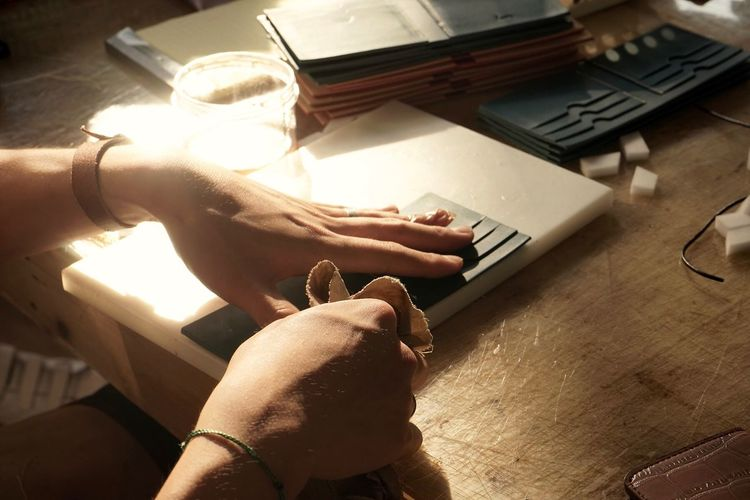 Cropped hands cleaning wallet on desk in office
