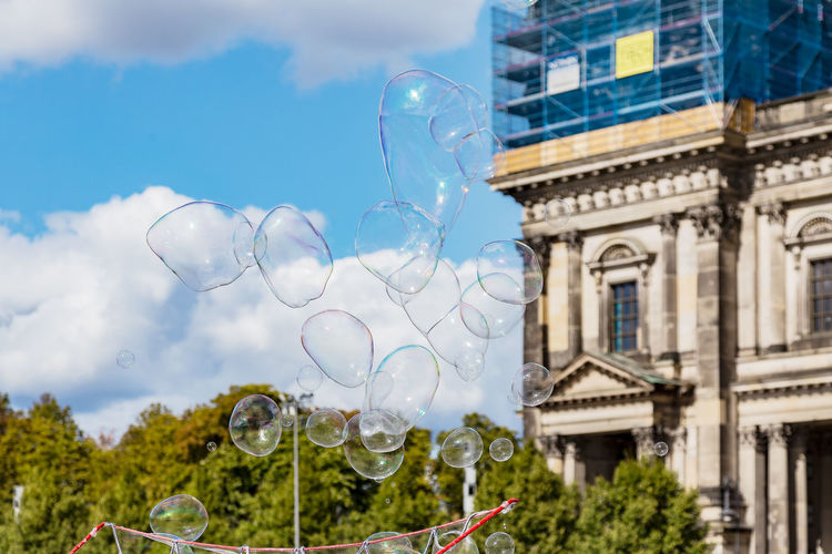 Low angle view of bubbles against buildings