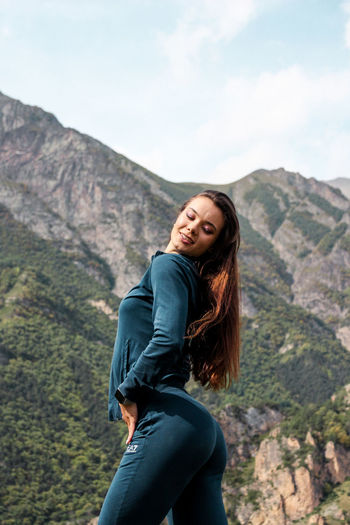 Side view of beautiful woman standing against mountain range