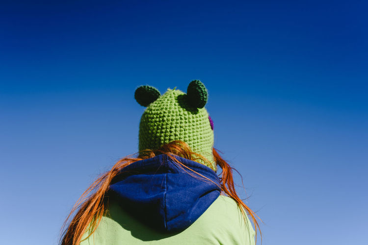 Rear view of woman against blue sky