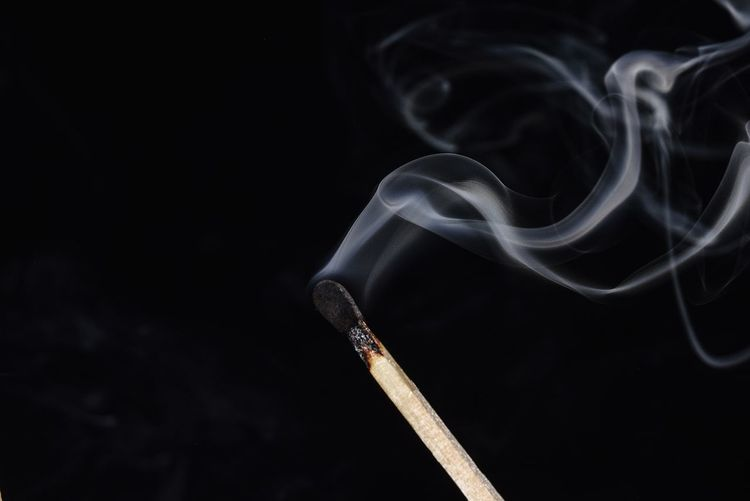 Close-up of matchstick smoke against black background