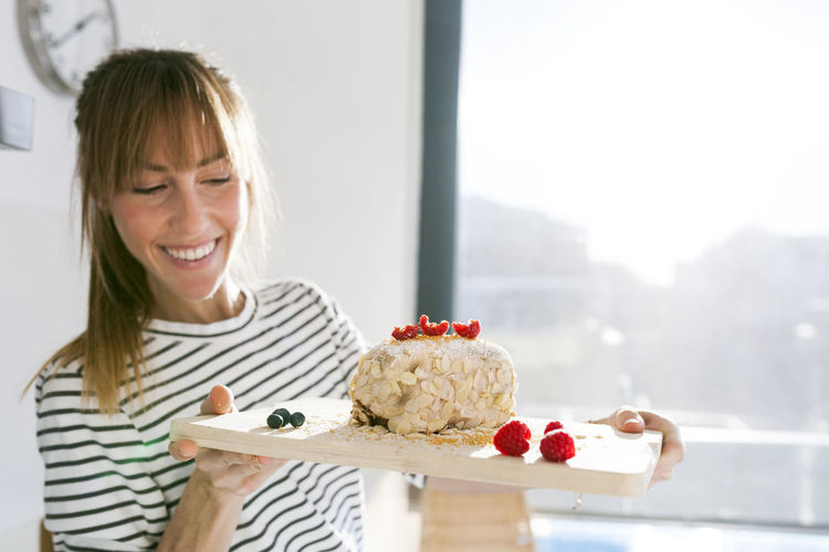 Portrait of smiling woman with ice cream on table