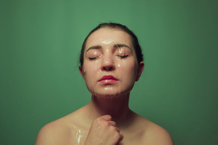 Close-up of shirtless young woman with beauty product on face against green background