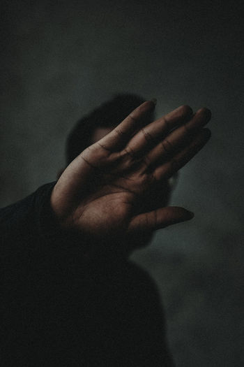 Close-up of man showing hand in darkroom