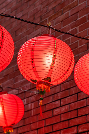 Low angle view of illuminated lanterns hanging on wall