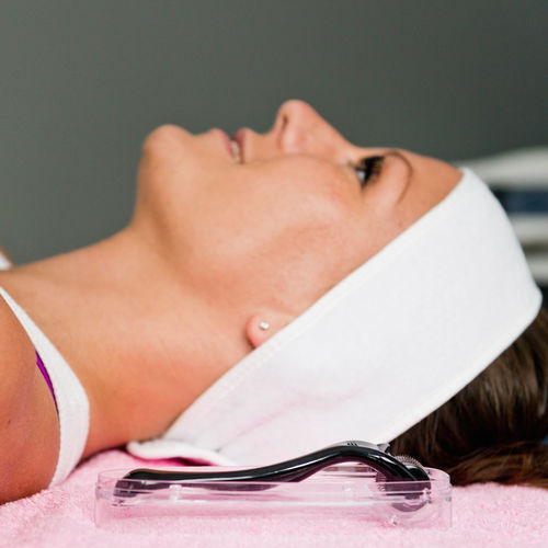 Close-Up Of Woman Lying Down By Cosmetic Roller At Spa