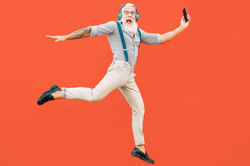 Senior man jumping outdoor person Hipster Senior Adult Senior Man Beard Pensioner Retirement Happy Colored Background Studio Shot Human Arm Full Length Red One Person Arms Raised Young Adult Jumping Indoors  Mid-air Red Background Young Men Lifestyles Adult Human Limb