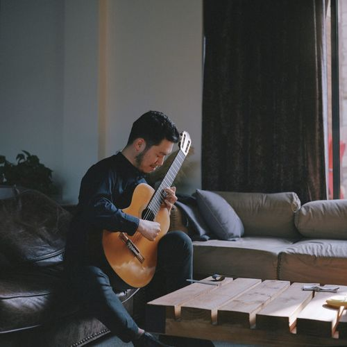 Man Playing Guitar While Sitting On Sofa At Home