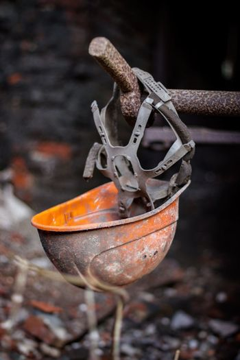 Close-up of abandoned hardhat hanging outdoors