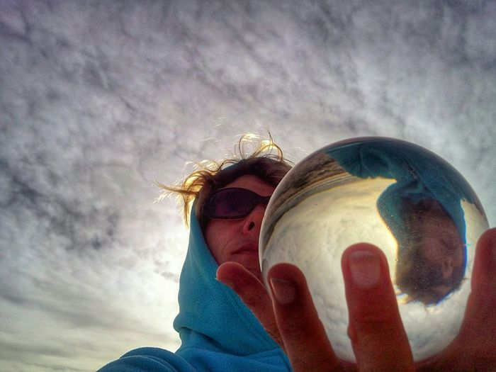 Low angle view of mid adult woman holding crystal ball with reflection
