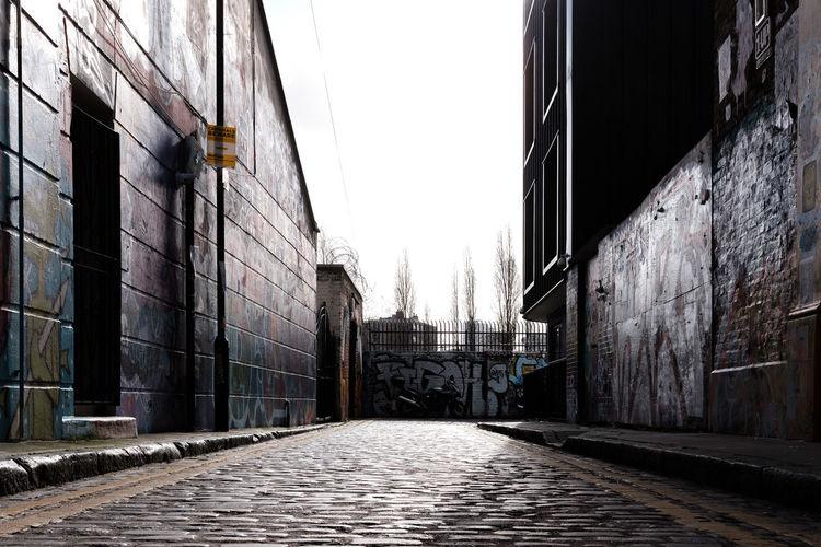 Narrow alley amidst buildings against clear sky