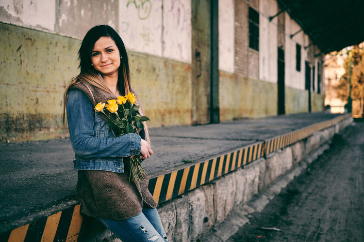 Women's Day Architecture Beautiful Woman Building Exterior Built Structure Casual Clothing City Flower Flowering Plant Focus On Foreground Front View Lifestyles Looking At Camera One Person Outdoors Plant Portrait Real People Rosé Smiling Women Yellow Young Adult Young Women