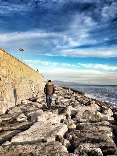 Rear view of man walking on rocks by sea against cloudy sky