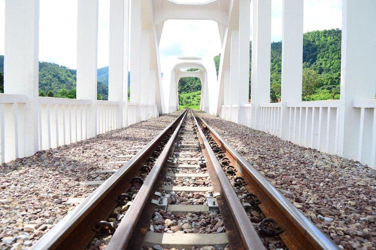 Railroad tracks amidst white columns