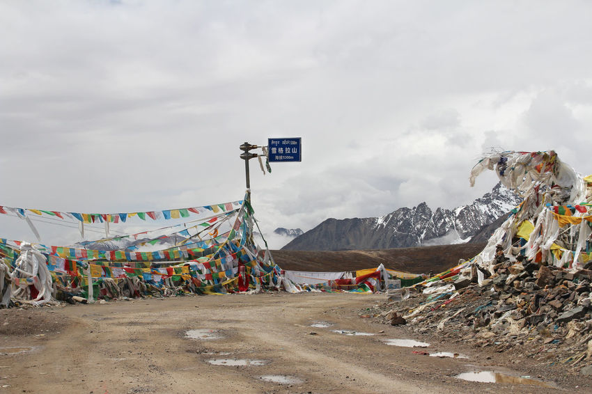 View of mountains with the prayer flags at XueGeLa mountain pass in Tibet, China Day Flag Mountain Mountain Range Multi Colored Nature No People Outdoors Road Sky Snow Tibetan Buddhism Tibetan Culture Tibetan Prayer Flags Travel Destinations
