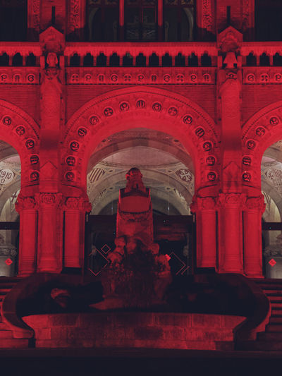 Statue of red outside building at night