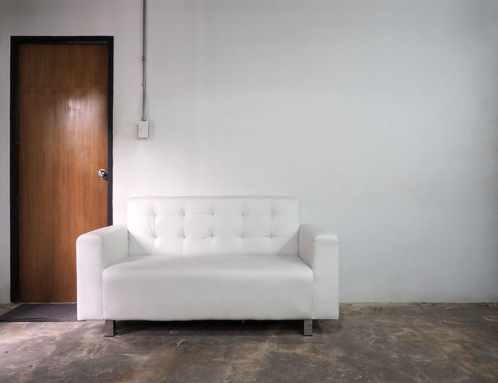 White leather sofa and white old wall and old wood door in room. Absence Architecture Day Door Doors Empty Furniture Home Interior Home Showcase Interior Indoors  Living Room Luxury No People Room Room; Sofa; Door; Interior; White; Living; Modern; Design; Couch; Wall; 3d; Contemporary; Home; Furniture; Empty; Minimalist; Wood; Apartment; Inside; Floor; Nobody; Render; House; Leather; Decoration; Light; Lifestyle; Relax; Comfortable; Seat; Classic;  Sofa
