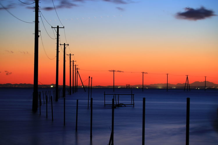 Silhouette of poles against sky during sunset