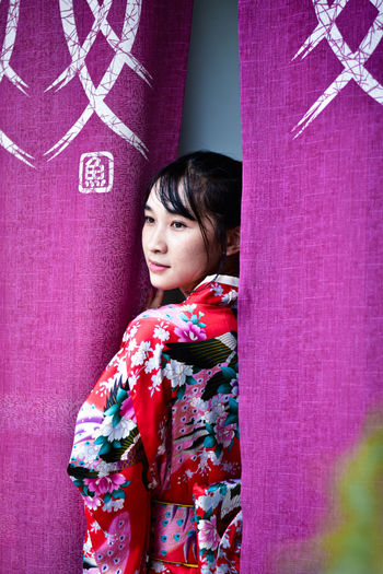 Young woman looking away standing admist pink curtain