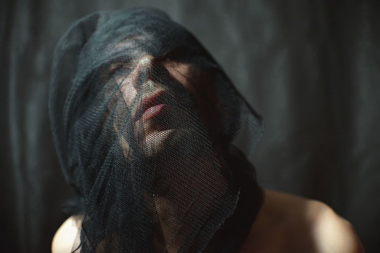 Close-up of man wrapping net over face at home