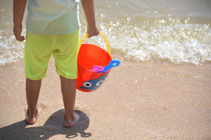 Beach Bucket Child Day Girl Kid Leisure Activity Low Section Nature One Person Only One Woman Only Outdoors People Sand Sand Pail And Shovel Sea Shadow Standing Summer Sunlight Tourism Vacations Walking Water Wave