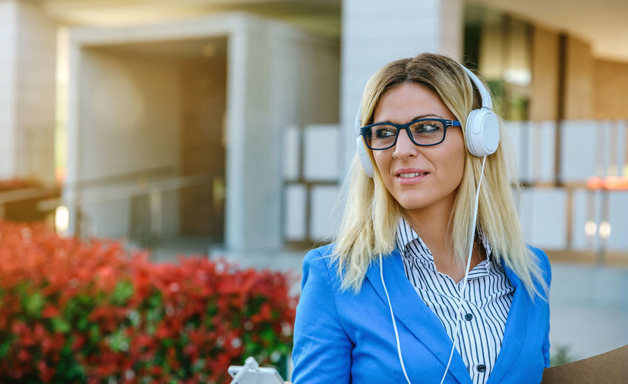 Businesswoman with headphones and mobile in the street Business Glasses Happy Headphones Horizontal Sunlight Woman Worker Working Business Finance And Industry Businesswoman Caucasian Dossier Executive  Flare Lifestyles Office Building One Person Outdoors Portfolio Real People Smart Phone Street Sun Young Adult