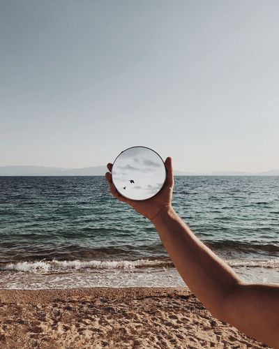 Mirroring the birds Mirror Effect Mirror Mirrored Mirror Reflection Sea Sky Water One Person Beach Hand Human Hand Horizon Human Body Part Clear Sky Lifestyles 2018 In One Photograph