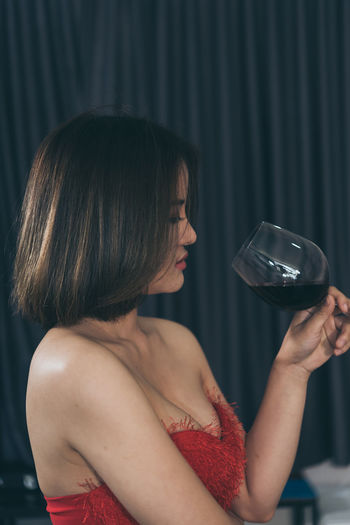 Close-up of woman drinking red wine against curtain