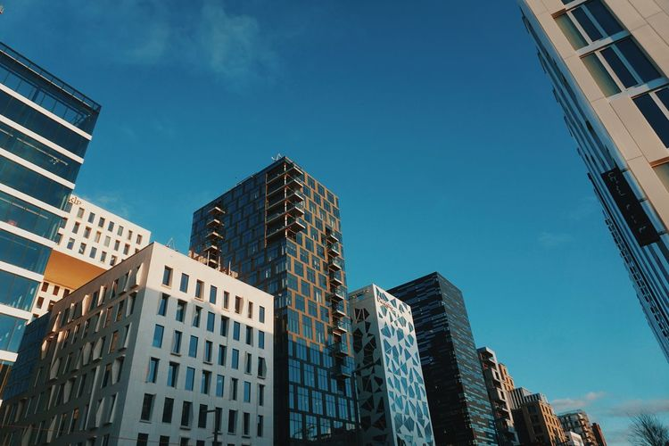 Low angle view of buildings in oslo against blue sky