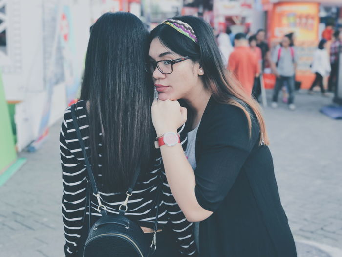 Side View Of Young Woman Leaning On Female Friend At Street