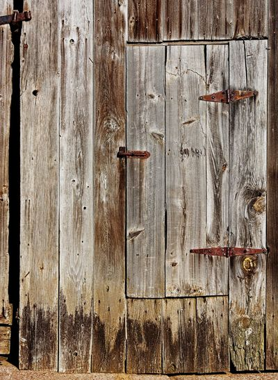 Door in a Door. One New England farmer plus tools = Yankee ingenuity. Why open the whole barn door when you can cut out a small one? The entrances to an abandoned tobacco barn in Ellington, Connecticut. Backgrounds Barn Close-up Connecticut Day Door Doors Farm Farm Life Farn Full Frame New England  No People Old Buildings Old-fashioned Outdoors Rural Rural Scene Wood Wood - Material