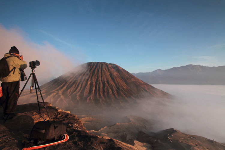 Rear view of man photographing at mt bromo