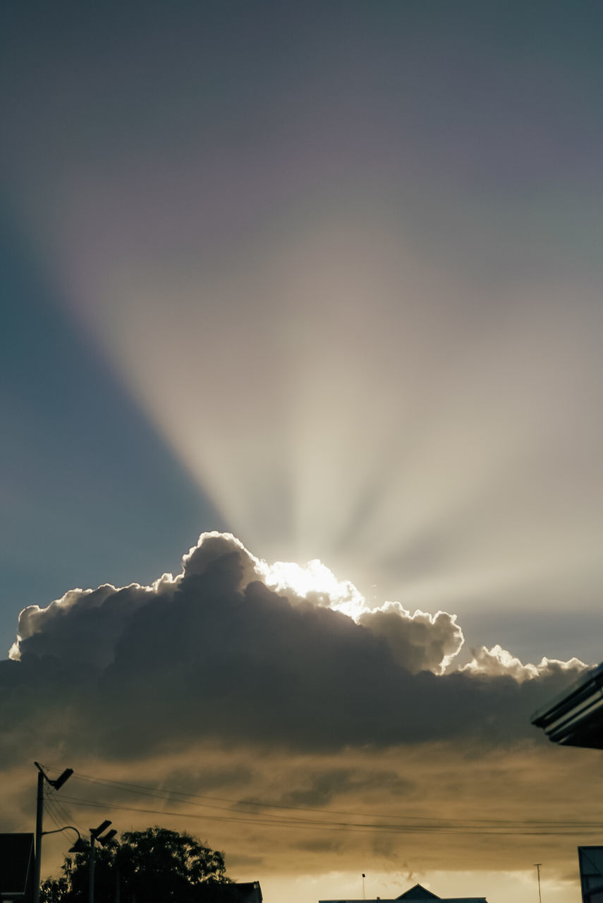 LOW ANGLE VIEW OF SUNLIGHT STREAMING THROUGH SILHOUETTE BUILDINGS AGAINST SKY