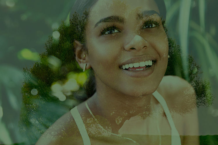Close-up of smiling young woman against glass