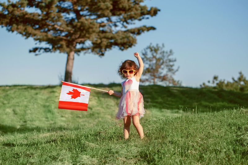 Cute girl holding canadian flag while standing on grass against trees and sky