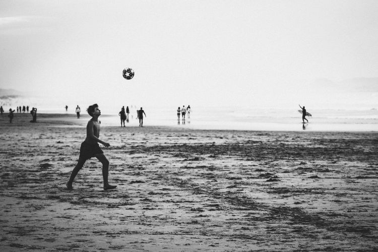 People playing soccer on beach