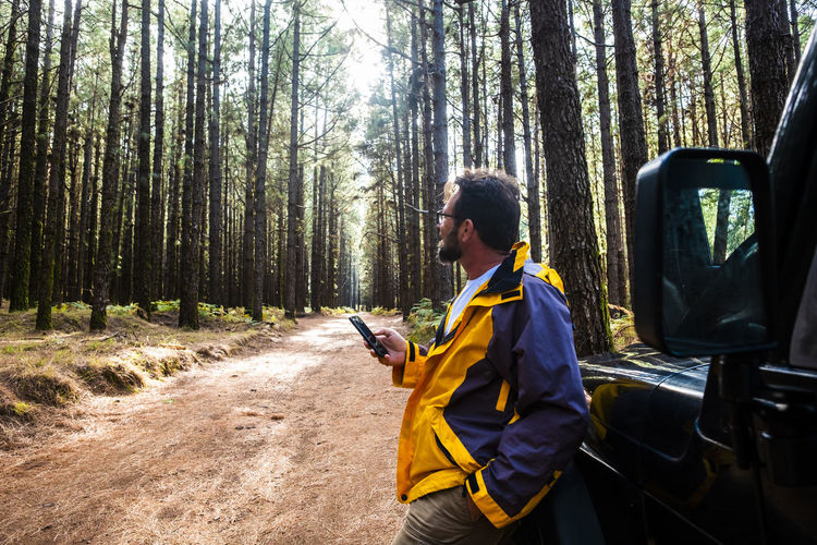 Young man using mobile phone in forest