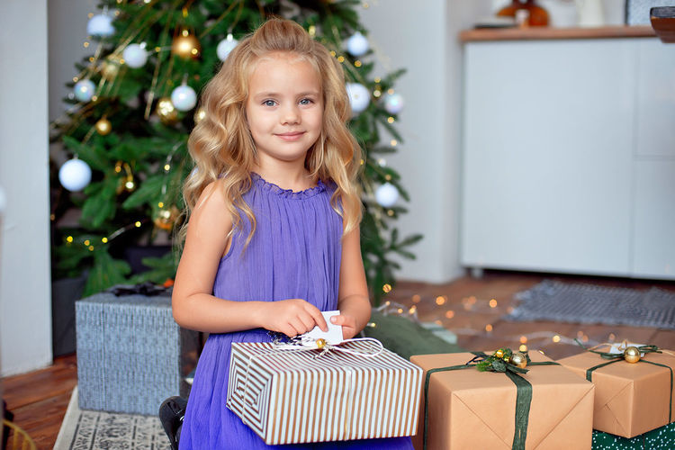 Portrait of smiling girl with gifts sitting against christmas tree at home