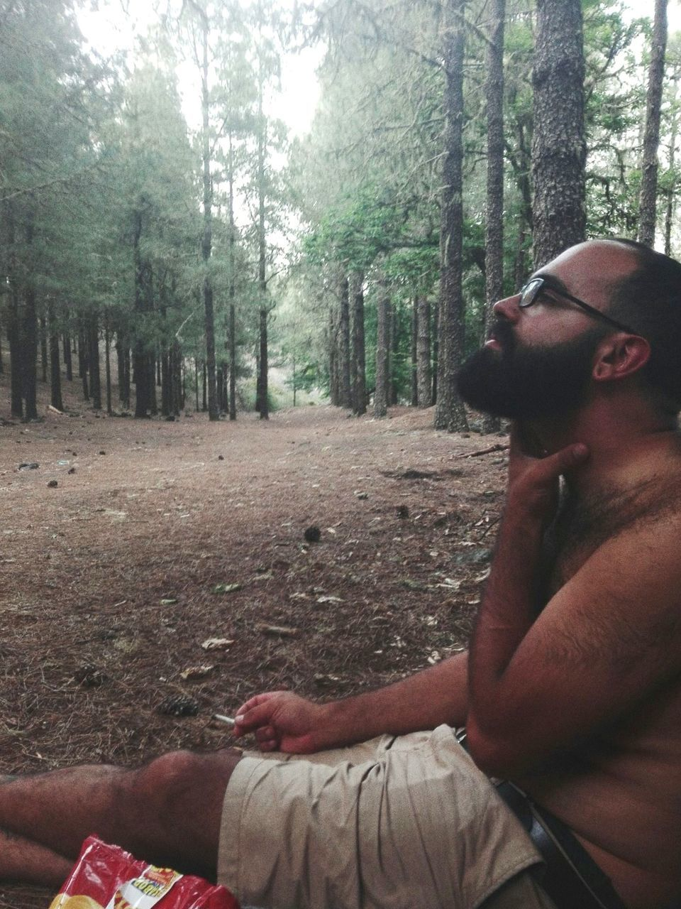 Side View Of Shirtless Man Sitting Against Trees In Forest