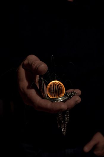 Cropped hands of man holding pocket watch with wire wool against black background
