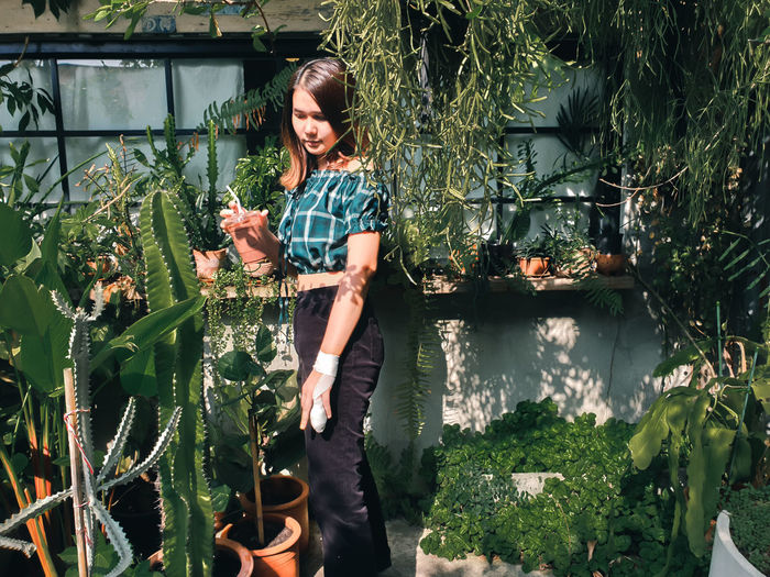 Full length of woman holding plants