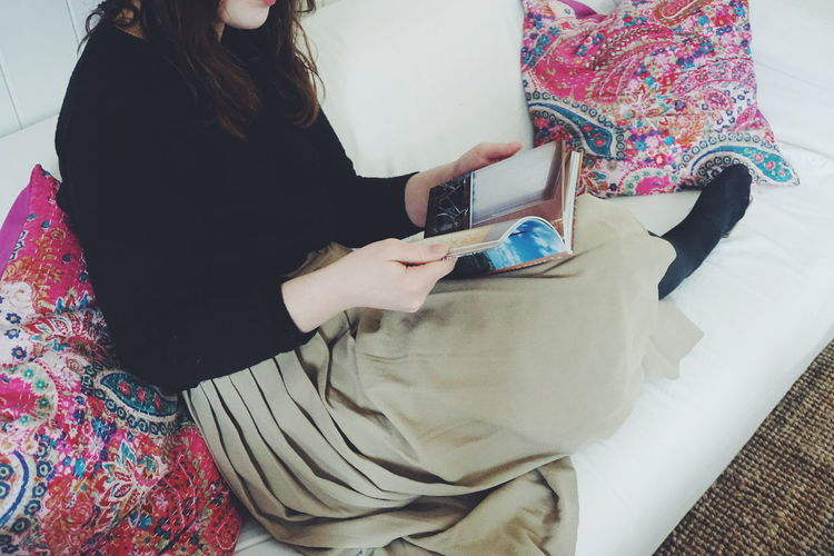 Young woman sitting on sofa Reading a book Close-up Human Body Part Midsection One Person One Woman Only People Read Readin Reading Reading & Relaxing Reading A Book Reading Time Relax Sofa Women Young Adult Young Women Place Of Heart