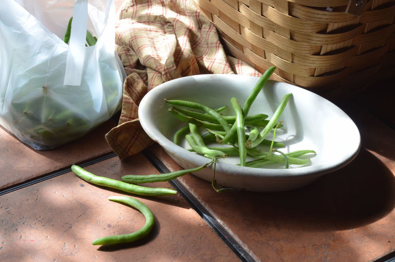 Green beans, white dish with prepared green beans ready for cooking, baske on outdoor table