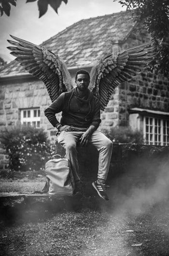 Portrait of man wearing costume wings while sitting on wall