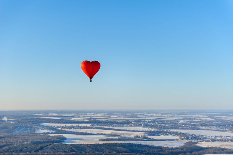 Aerial view of red heart shape hot air balloon against blue sky