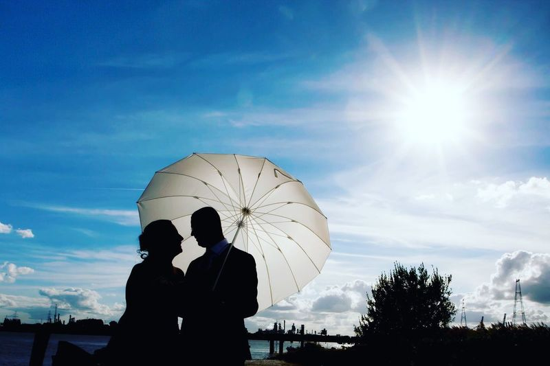 Two people in love looking at each other in the summer sun, under a parasol Couple Love Bonding Cloud - Sky Couple - Relationship Day Friendship Leisure Activity Lifestyles Men Nature Outdoors People Real People Silhouette Sky Standing Sun Sunlight Togetherness Tree Two People Women