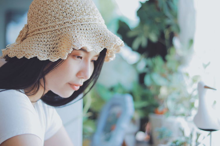 Thoughtful young woman wearing hat while looking away at home