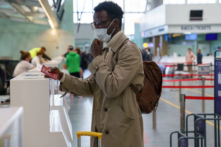 Man wearing mask while standing at airport
