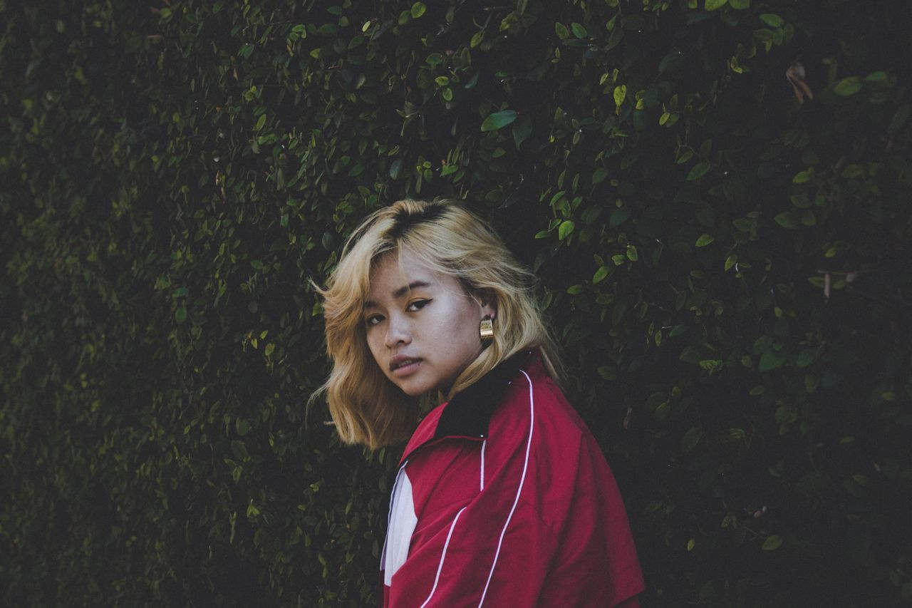 one person, blond hair, real people, portrait, red, outdoors, looking at camera, young adult, standing, young women, day, tree, people